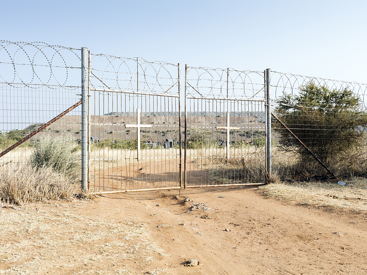 Entrance to the graveyard of Ga-Molekane Village with the RPM Mogalakwena Mine dump, Mapela, Limpopo, Northern Limb